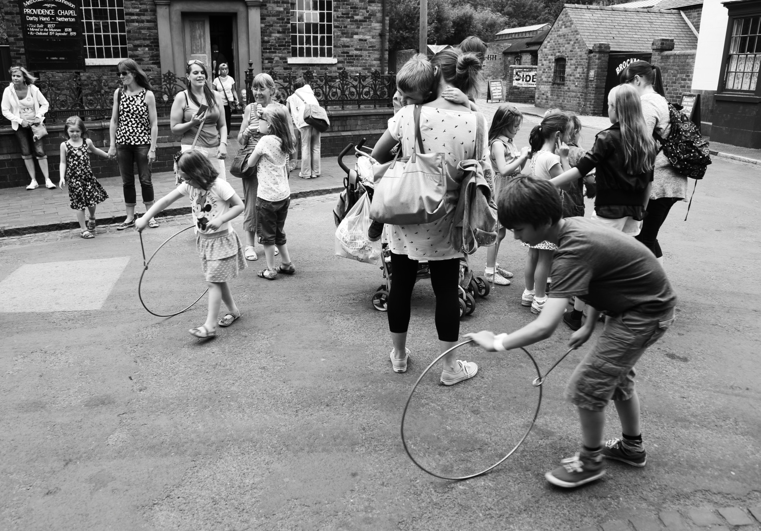 Children playing with metal hoop toys 1900s